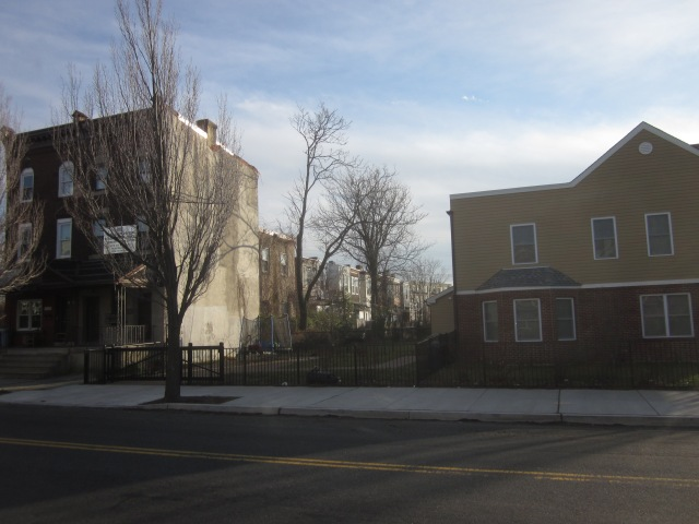 3101 Glenwood can be seen from behind one of the new townhomes at 32nd & Cecil B. Moore