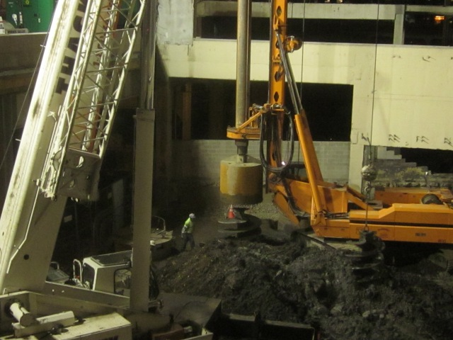 Positioning the large drill bit to dig a hole for foundation support columns