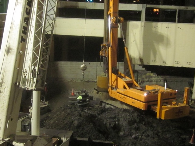 Large drill bit being lowered into the ground to dig a hole for support columns