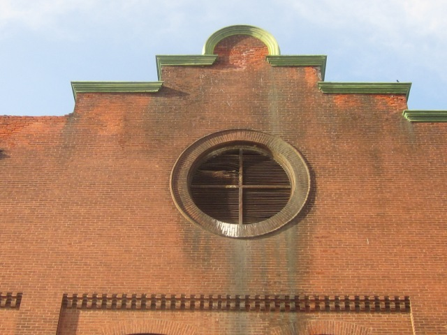 Stepped roof and circular vent in the brick facade of 1221 Mt. Vernon Street