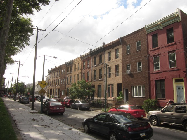 Townhouses, including brownstones, on Tasker Street on the north side of the park