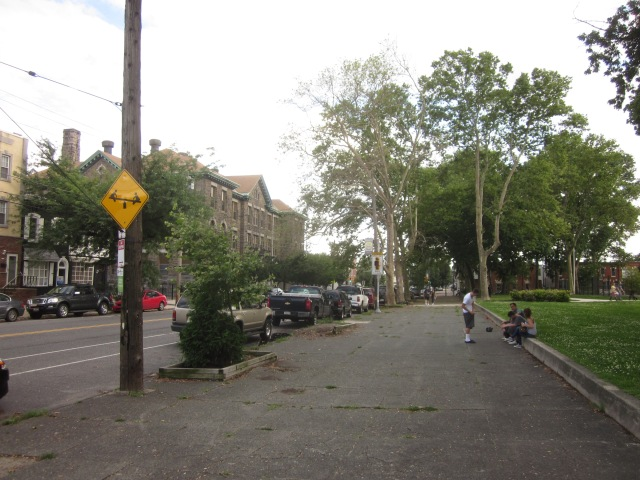 Looking down the wide sidewalk on Moyamensing Avenue, on the park's eastern side