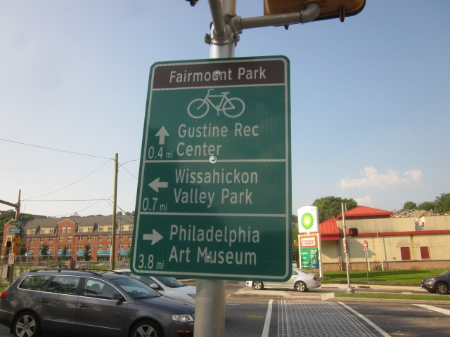 Bike path sign gives directions to important locations and landmarks